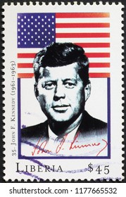 Milan, Italy – July 27, 2018: President John F. Kennedy and flag on postage stamp