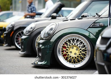 "MILAN, ITALY - JULY 28, 2015: Colored and personalized Mini Cooper ""John Cooper Works"" tuning cars exposed at public parking. Close up of big tuned car wheel in gold color on Milan, July 28, 2015"