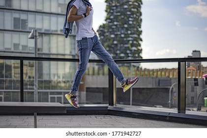 Milan, Italy - July 4, 2020: boy wearing Pharrell Williams Human Race Body and Earth NMD by Adidas and jumping on the street - illustrative editorial