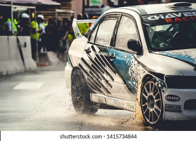 Milan, Italy, June 02, 2018: closeup on wheels of a Mitsubishi Lancer Evolution in action on wet asphalt during a rally race at the Iper Drive in Milan.
