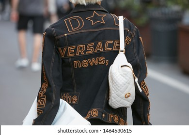 MILAN, ITALY - JUNE 15, 2019: Man with black denim Versace jacket and white pouch before Versace fashion show, Milan Fashion Week street style