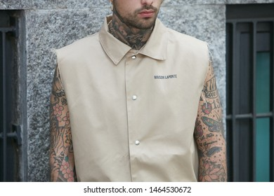 MILAN, ITALY - JUNE 15, 2019: Man with beige Maison La Ponte shirt and tattoes before Emporio Armani fashion show, Milan Fashion Week street style