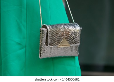 MILAN, ITALY - JUNE 15, 2019: Woman with Emporio Armani silver leather bag and green dress before Emporio Armani fashion show, Milan Fashion Week street style