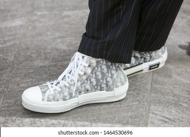 MILAN, ITALY - JUNE 15, 2019: Man with white Dior sneakers and pinstripe trousers before Emporio Armani fashion show, Milan Fashion Week street style