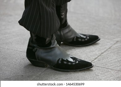 MILAN, ITALY - JUNE 15, 2019: Man with black leather cowboy boots before Emporio Armani fashion show, Milan Fashion Week street style