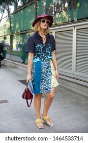 MILAN, ITALY - JUNE 15, 2019: Woman with blue floral dress design before Emporio Armani fashion show, Milan Fashion Week street style