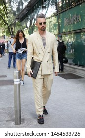 MILAN, ITALY - JUNE 15, 2019: Man with beige suit and sunglasses before Emporio Armani fashion show, Milan Fashion Week street style