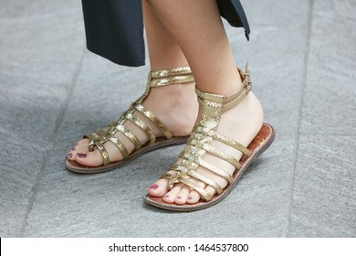 MILAN, ITALY - JUNE 15, 2019: Woman with golden reptile leather sandals before Emporio Armani fashion show, Milan Fashion Week street style