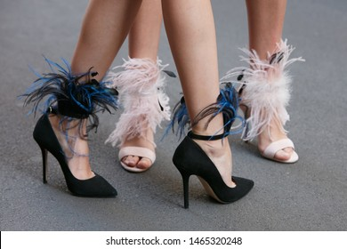 MILAN, ITALY - JUNE 15, 2019: Women with black and pink high heel shoes with feathers before Versace fashion show, Milan Fashion Week street style