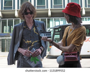 MILAN, ITALY -JUNE 16, 2018: Asian woman interviews eccentric man in the street before MARNI fashion show, during Milan Fashion Week Men and women spring collections. collections.