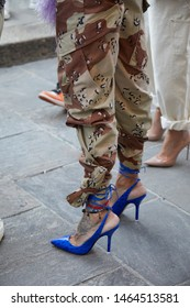 MILAN, ITALY - JUNE 16, 2019: Woman with blue high heel shoes and military trousers before Palm Angels fashion show, Milan Fashion Week street style