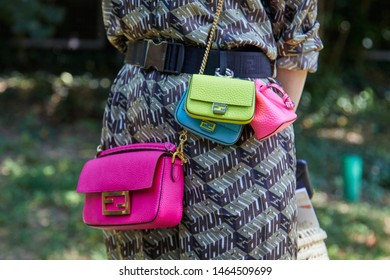 MILAN, ITALY - JUNE 17, 2019: Woman with pink, blue and yellow Fendi bags before Fendi fashion show, Milan Fashion Week street style