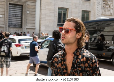 MILAN, ITALY - JUNE 18: Fashionable man poses outside Ferragamo fashion show during Milan Men's Fashion Week on JUNE 18, 2017 in Milan.
