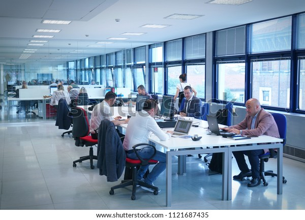 Milan, Italy - June 2018: Business people in an open space office interior with a panoramic window