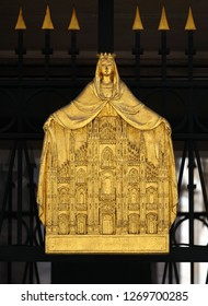 MILAN, ITALY - JUNE 22, 2018: Gilded plaque depicting the Madonna with her cloak shielding a gold relief model of Milan cathedral, Duomo di Santa Maria Nascente, Milan, Italy