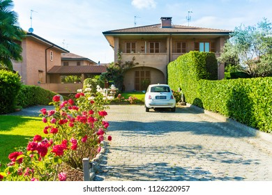 MILAN, ITALY  - JUNE 22 : Traditional Italian Style House with Garden with Blooming Roses and Italian Fiat Car Parked in Front of the House