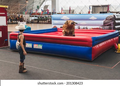 MILAN, ITALY - JUNE 22: Young cowboy and mechanical bull at Rocking The Park, event dedicated to American music and lifestyle of the 40s, 50s and 60s on JUNE 22, 2014 in Milan.