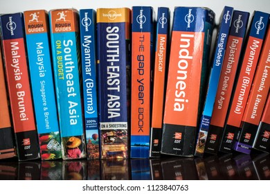 Milan, Italy - June 30, 2018: Mixed brands and countries used travel guides on a home bookshelf. Concept for prepare your trip, adventure, backpacking, taking a gap year, go round the world