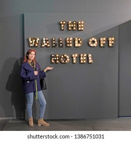 "Milan, Italy - March 21, 2019:  Beautiful girl presenting ""The walled off Hotel"" in a Banksy unauthorized exhibition"