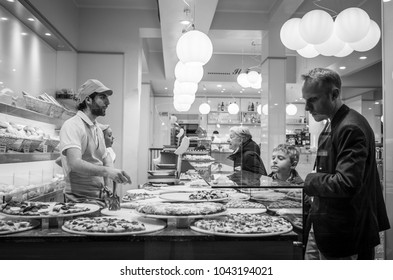 Milan, Italy - March 23, 2016:  Customers in pizzeria choosing the piece of italian pizza    in Milan, Italy