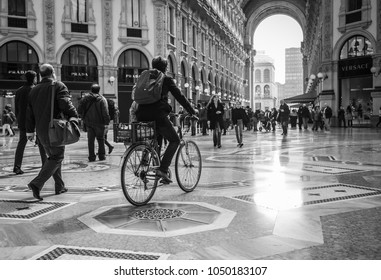 Milan, Italy - March 23, 2016:  Man rides a bicycle in the center of Milan in Galleria Vittorio Emanuele II in Milan, Italy