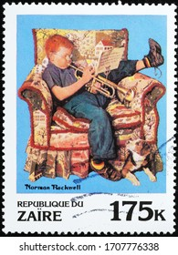 Milan, Italy - March 25, 2020: Boy playing trump by Norman Rockwell on stamp