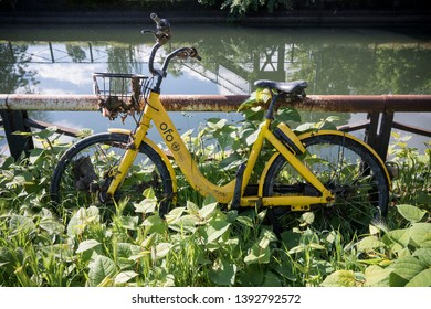 Milan, Italy - May 09, 2019: A broken yellow Ofo bike abandoned near Naviglio water canal. Ofo interrupted the bike sharing service in Milan for vandalism against his bicycles.