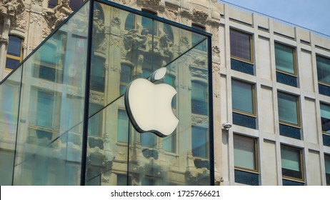 Milan, Italy, May 1, 2020: Deserted streets of the city during quarantine in Milano. Corona virus COVID19. Closed sails of shops. Pandemic. Liberty square Apple store. Logo. Noise artificial
