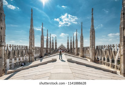Milan, Italy - May 16, 2017: People visit the Milan Cathedral roof or Duomo di Milano. Milan Cathedral is the main tourist attraction of Milan. Panoramic view of Gothic spires with statues of Duomo.