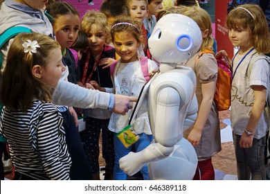 Milan, Italy - May 22, 2017: A group of children together with a Pepper robot