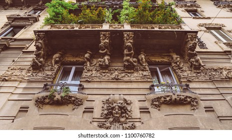 Milan, Italy - May 24, 2018: Facade of building in Porta Venezia neighbourhood. Ornamental humanist statues hanging from the wall. Architecture is early 1900s nature inspired Liberty, art-noveau style