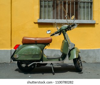 Milan, Italy - May 27, 2018: Green Piaggio Vespa LML T5 150 parked on side of street with yellow background