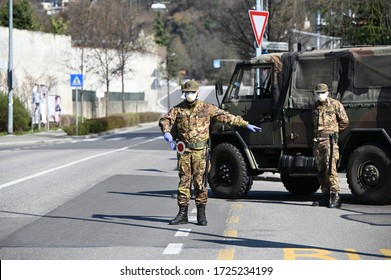 MILAN, ITALY - MAY 8, 2020. Military soldier controls. Security patrol with masks and gloves monitor passing motorists. Daily street control for the Covid-19 global crisis. The army at work.