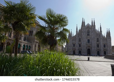 Milan, Italy - May 9, 2020:  Empty Duomo square, flowerbed in front of Duomo cathedral. Few people walk and Police standing by van, during coronavirus epidemic period. Second phase of quarantine