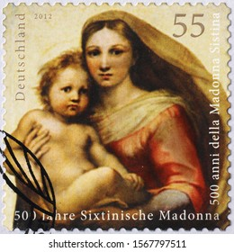 Milan, Italy - November 09, 2019: Madonna and Jesus by Raphael on postage stamp
