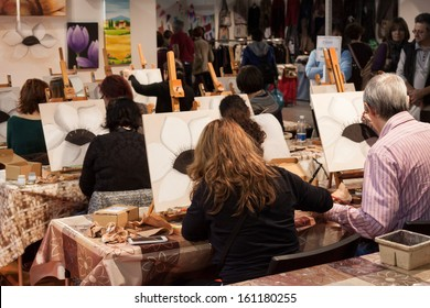 MILAN, ITALY - NOVEMBER 1: People take a painting at Weekend Donna 2013, event dedicated to women and their passions on NOVEMBER 1, 2013 in Milan.