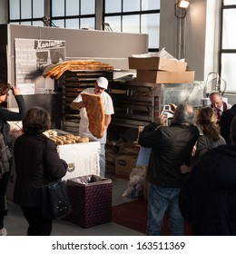 MILAN, ITALY - NOVEMBER 16: Baker prepares flat bread at Golosaria, important event dedicated to culture and tradition of quality food and wine on NOVEMBER 16, 2013 in Milan.