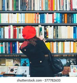 MILAN, ITALY - NOVEMBER 20, 2015: Rear view of a woman choosing a book on a shelves in a book shop