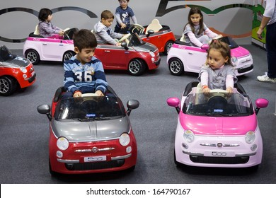 MILAN, ITALY - NOVEMBER 22: Children drive electric cars at G! come giocare, trade fair dedicated to games, toys and children on NOVEMBER 22, 2013 in Milan.