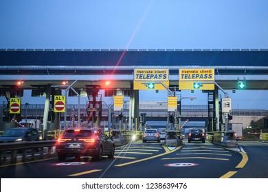 Milan, Italy - November 23, 2018: cars pass through illuminated Telepass toll gates on Italian highway at dawn.