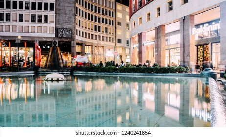 Milan, Italy - November 25, 2018: Long exposure of shoppers at Piazza San Babila Central Square with Fountain Water the City Center of Milan,Italy