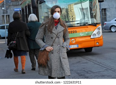 Milan - Italy november 6,2018 - smog and atmospheric pollution, pm 10 - girl with antismog mask in the city in urban traffic