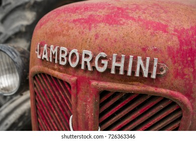 MILAN / ITALY - OCTOBER 01, 2017: old Lamborghini logo sign on a red vintage rusty farm tractor