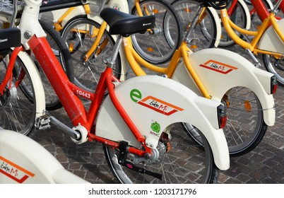 MILAN, ITALY - OCTOBER 10, 2018: A selective focused row of Bike Mi, the colorful public bicycles of Milan City, now also available as e-bike in electric version