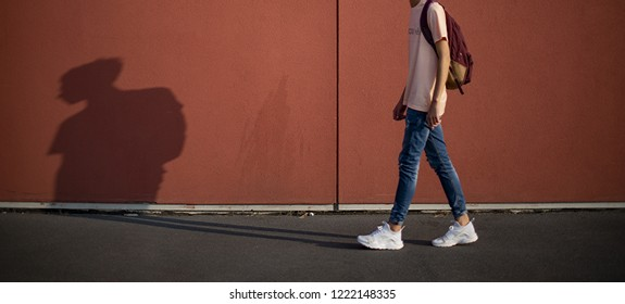 Milan, Italy - October 13, 2018: teenager with backpack wearing a pair of white Nike Huarache