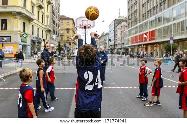MILAN, ITALY -OCTOBER 14: Children playing basketball in the streets during an ecological sunday with no cars around in Milan October 14, 2012.