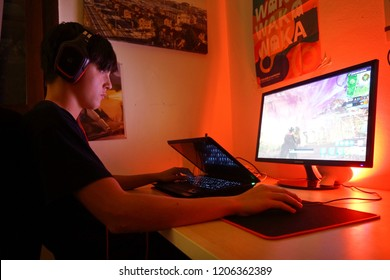 Milan, Italy - October 2018: Teenager playing Fortnite video game in the his bedroom by night.