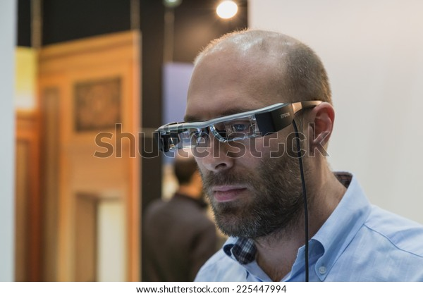 MILAN, ITALY - OCTOBER 22: Man wearing glasses for augmented reality at Smau, international exhibition of information communications technology on OCTOBER 22, 2014 in Milan.