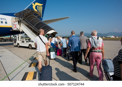 MILAN, ITALY - SEPTEMBER 15, 2015: Back view of people carrying luggage boarding on a Ryanair plane. Ryanair is the biggest low-cost airline company in the world.