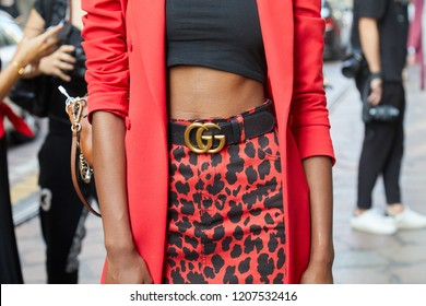 MILAN, ITALY - SEPTEMBER 20, 2018: Woman with red jacket, dappled skirt and Gucci belt before Vivetta fashion show, Milan Fashion Week street style